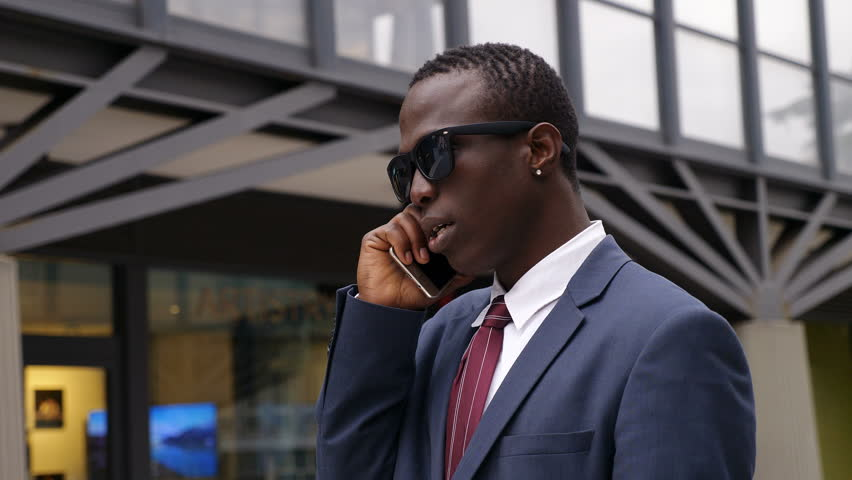 Busy confident black african manager talking by phone in the street | Shutterstock HD Video #1009768670