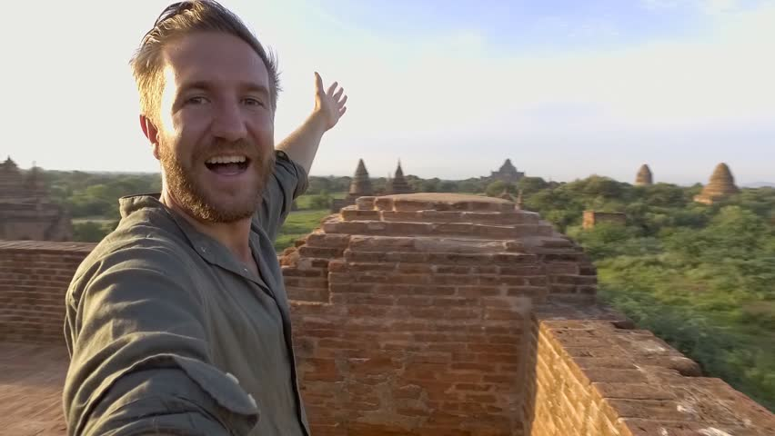 360 degree selfie, man takes a selfie point of view turning 360 degrees with camera. Young man traveller taking selfies on top on ancient Buddhist temple in Bagan Myanmar.  | Shutterstock HD Video #1009774100