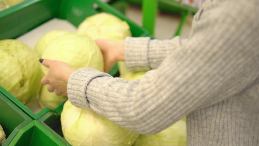 Young woman in the vegetable department of a supermarket chooses a cabbage. | Shutterstock HD Video #1009774460