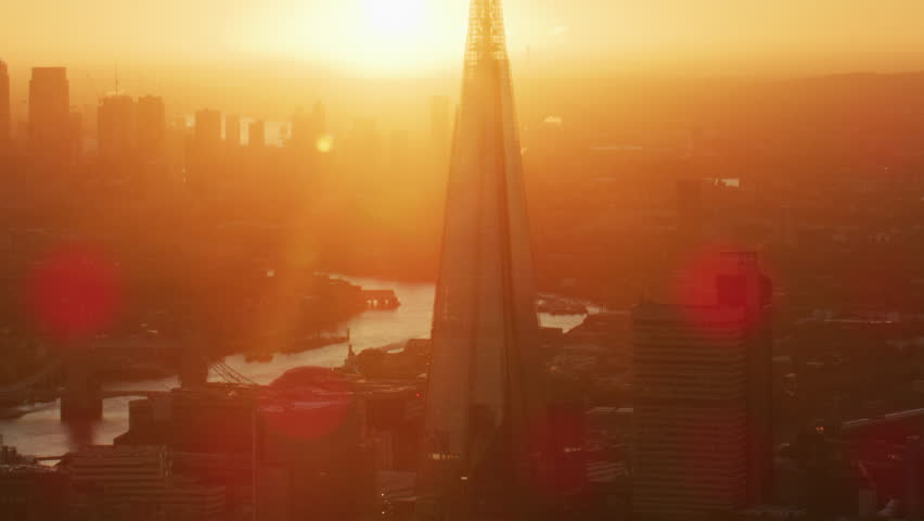 London UK - November 2017: Aerial sunrise view with sun flare London cityscape The Shard Tower Bridge River Thames Canary Wharf England UK RED WEAPON