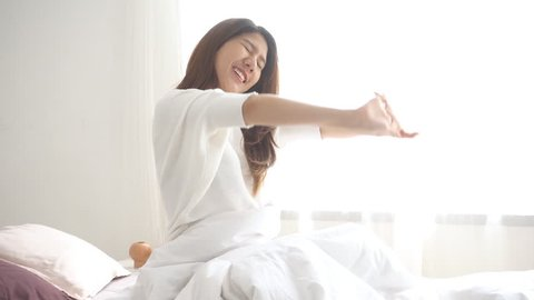 Slow motion - Happy beautiful young Asian woman waking up in morning, sitting on bed stretching in cozy bedroom looking window. Funny asian woman after wake up. Asia woman is stretching and smiling.