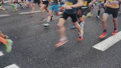 Huge crowd of athletes and sports enthusiasts run past camera on start or finish line of big event or competition, during marathon or race. Wear sports equipment clothing. healthy lifestyle activity