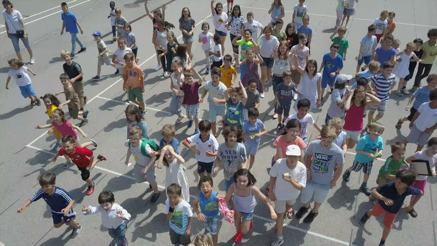 VIENNA AUSTRIA - CIRCA SEPTEMBER 2017: Crowd of Happy children in school playground of French high school running towards a drone