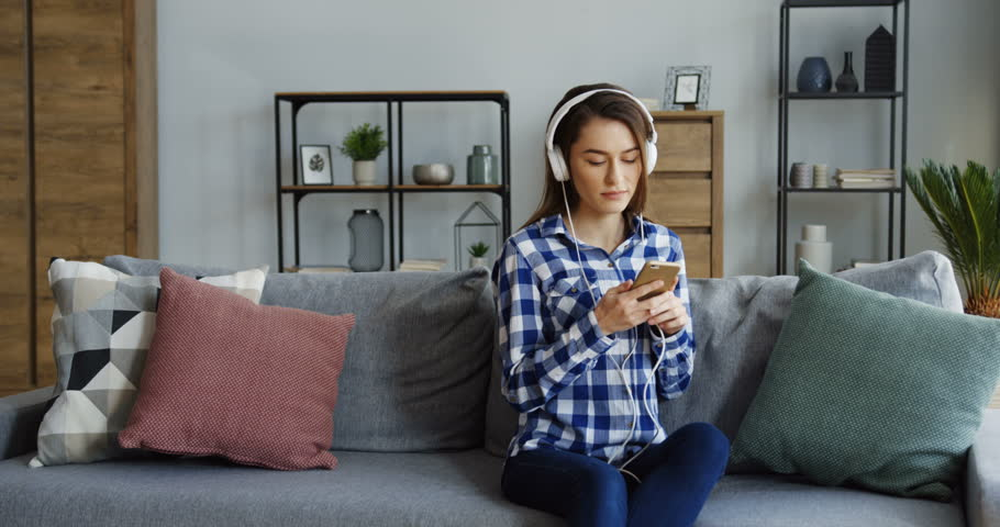 Young beautiful woman in the motley shirt and in headphones listening to the music on the smartphone and moving in the cozy home. Indoor | Shutterstock HD Video #1009827800