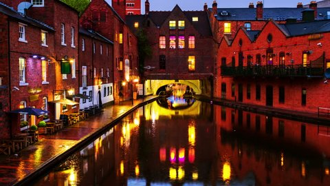 Birmingham, UK. Embankments during the rain in the evening at famous Birmingham canal in UK. Cloudy blue sky. Time-lapse at night. Zoom in