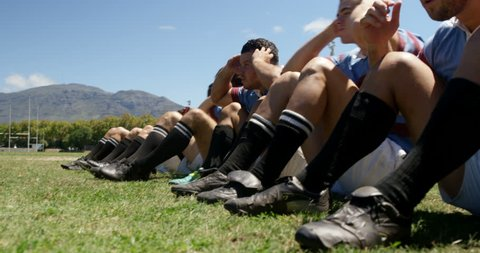 Determined rugby players doing crunches in the field 4K 4k