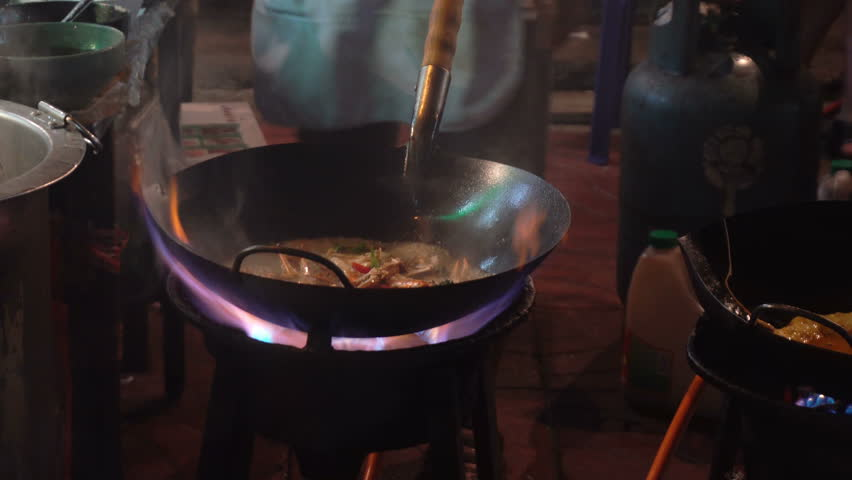 Street-side wok fire in Chinatown Bangkok. Cook fired up hot oil with vegetables outside on the road at night in downtown Yaowarat road food street in Thailand.   Shutterstock HD Video #1009871930