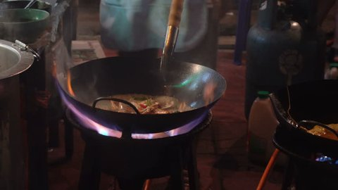 Street-side wok fire in Chinatown Bangkok. Cook fired up hot oil with vegetables outside on the road at night in downtown Yaowarat road food street in Thailand.
