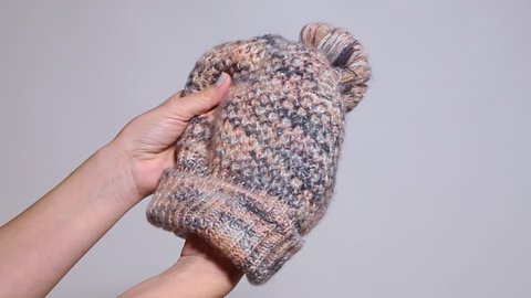 Woman holds cute warm winter hat in hands isolated at grey background.