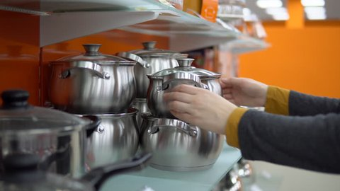 A young woman in a gray cardigan chooses a steel saucepan in the kitchen utensils department at the supermarket.