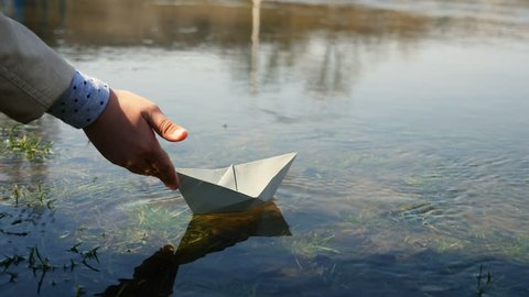 Child at the pond with a paper boat. A child starts up a paper boat. Close-up the hand and the paper boat