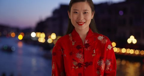 d05510cc5 Portrait of Asian millennial wearing red traditional Chinese outfit and  smiling for camera in Europe.