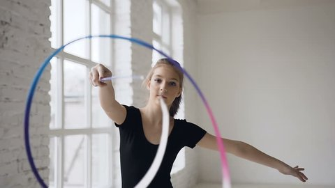 Portrait of graceful gymnastics spinning the colored ribbon in front of camera in the white studio on the window background and looking at the camera, slow motion
