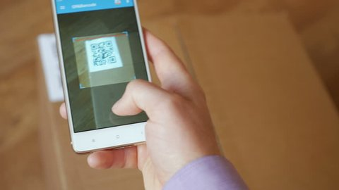 Scanning QR code with smart phone. The man reads the bar code using the application on the smartphone.