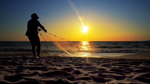 Unrecognizable silhouette fisherman fishing net on the sunset beach; cinematic steadicam shot