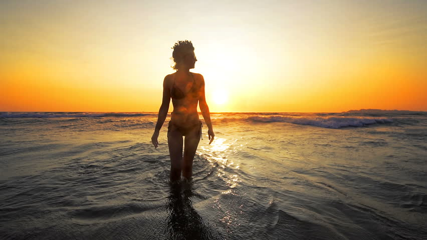 Silhouette of a sensual woman at sunset on the beach, sexy body, perfect figure, cinematic shot, SLOW MOTION #1009923860