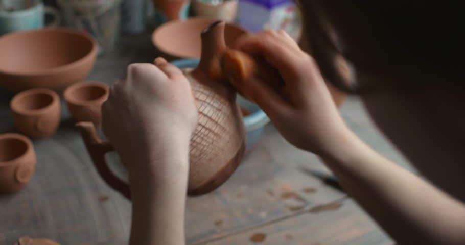 production process of pottery. The potter finally forms and applies textures to the clay kettle.  #1009932050