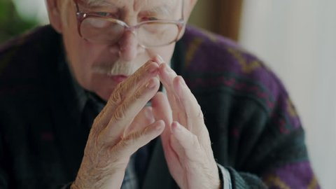 Worried old man banging his fingers together. Worried old man banging his fingers together before suddenly moving to the side with an intense expression to start a conversation.