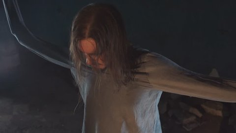 Crazy long haired caucasian man with straitjacket sleeves tied to ceiling struggling and yelling in abandoned building