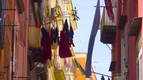 Colored clothes drying on the balcony of an old house in Italian city