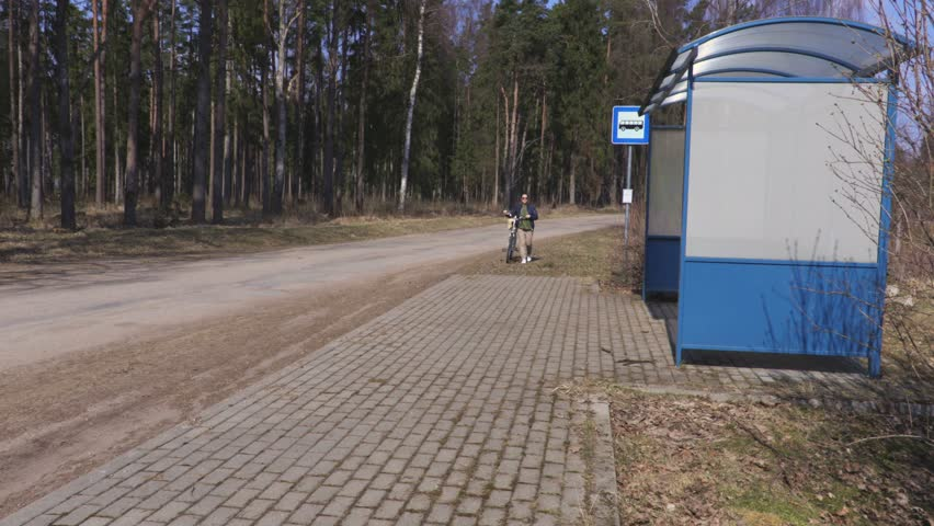 Woman with bicycle walking near bus stop