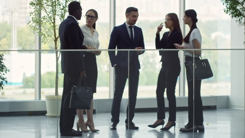 PAN of businesspeople standing in lobby and discussing ideas after conference   Shutterstock HD Video #1009942700