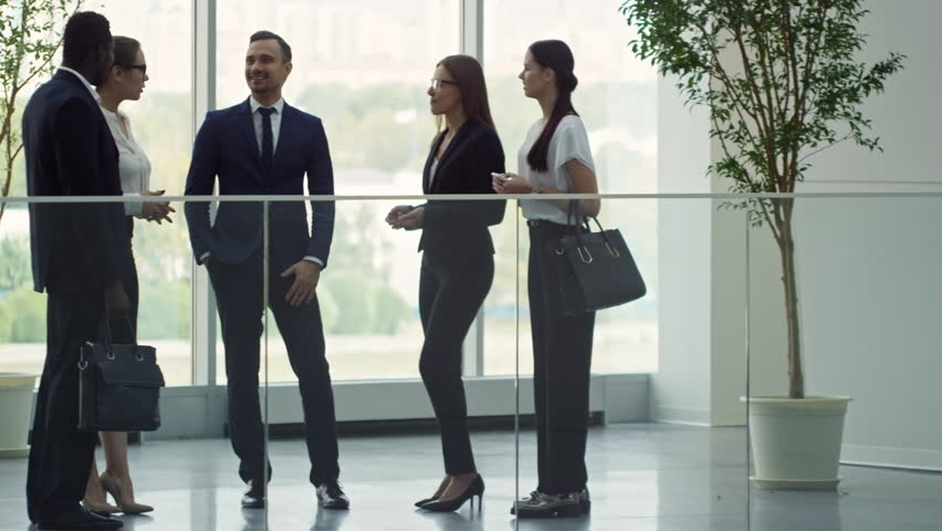 PAN of cheerful businesswomen and businessmen standing in lobby and chatting after conference   Shutterstock HD Video #1009943060