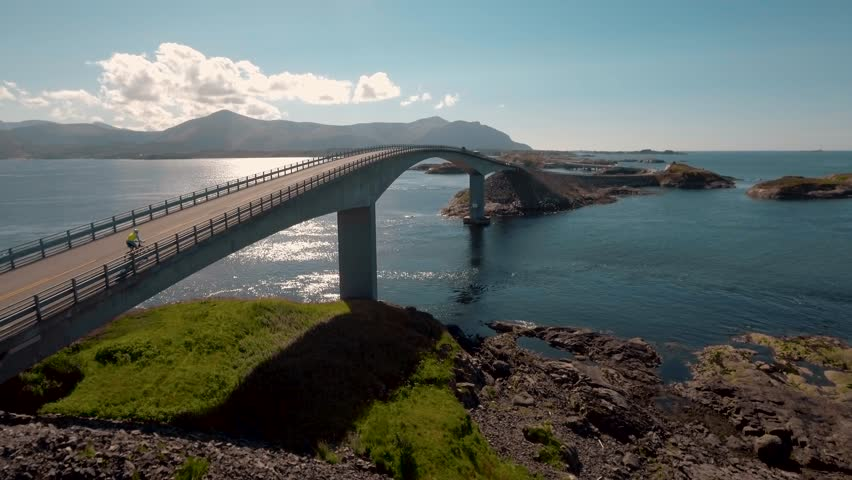 """Aerial view of cyclist on Atlantic Road (Atlanterhavsveien) also known as """"The Road in the Ocean"""" in Norway. National Tourist Route."""