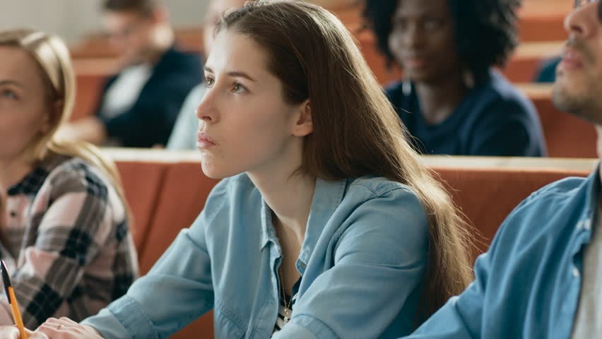 Beautiful Young Girl Listening to a Lecture in a Classroom. Diverse Group of Multi Ethnic Students Study at the University.    Shutterstock HD Video #1009955660