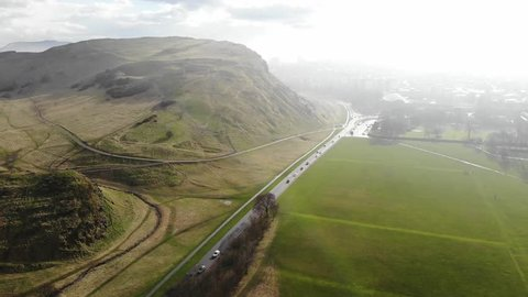 Aerial drone footage cityscape view of The Holyrood Park in cloudy day, Edinburgh, Scotland, United Kingdom.