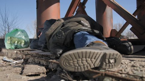 Close-up of homeless man's feet in boots, sleeping outdoors on the ground under the bridge in cold weather. Poor beggar covering himself with jacket. Homelessness and social issues concept. Dolly shot