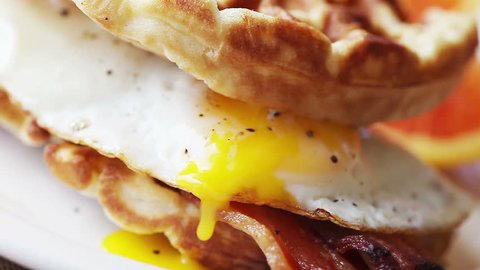 Peppered fried egg yolk drips slowly from a bacon and waffle sandwich