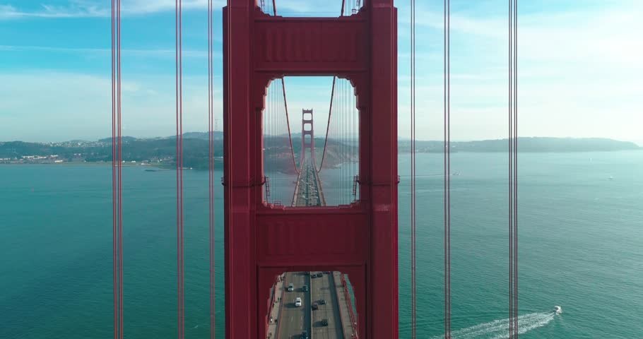 Aerial video of the Golden Gate Bridge. Inspirational drone flight through the window of the red tower above the busy road. San Francisco downtown on the background at sunset. California, USA. 4K | Shutterstock HD Video #1009987190