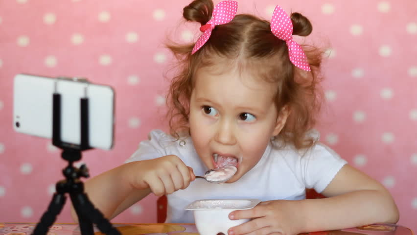 A little cute girl eats food and watches cartoons on the mobile phone. Child and gadgets, applications, internet, games.   Shutterstock HD Video #1009989290