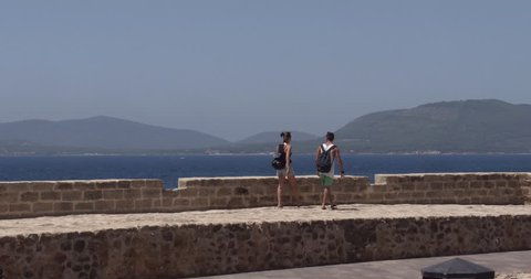 ALGHERO, SARDINIA, ITALY – JULY 2016 : Video shot of couple walking on city walls in central Alghero on a sunny day with amazing landscape in view