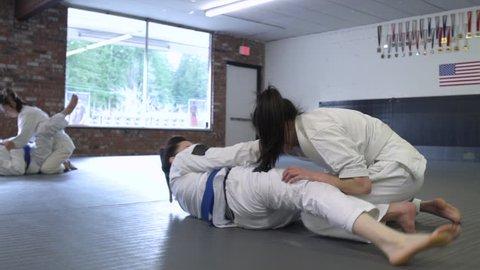 Young people doing Jiu-jitsu in a dojo