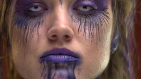 Makeup in purple tones on a crazy girl with pigtails, body painting