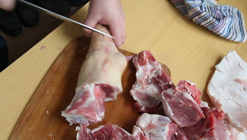Man holding knife with hands, cutting, chopping, preparing pig  raw, fresh meat steak for barbecue. Close up video footage of butcher cutting raw red bbq meat on cutting board.