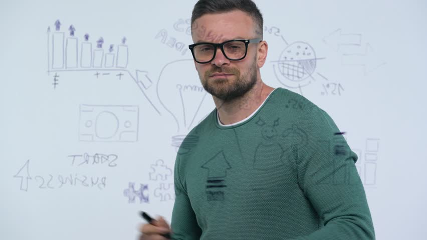 Man draws various growth charts, calculating prospects for success in a modern glass office | Shutterstock HD Video #1010087240