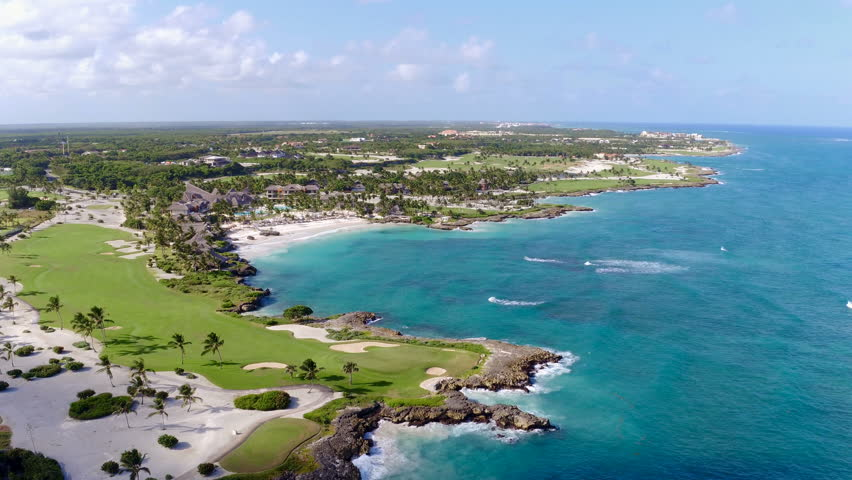 Aerial view flying over tropical blue ocean towards beautiful green mountains and white sandy beach. Dominican Republic. Punta Cana beach. Palms beach. Island top view. Beautiful place.