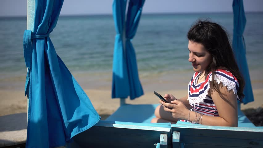 Girl texting in blue beach lounge. Young brunette woman lying on sunlounger, texting with her phone. Shot at Thassos island, Greece. | Shutterstock HD Video #1010098580