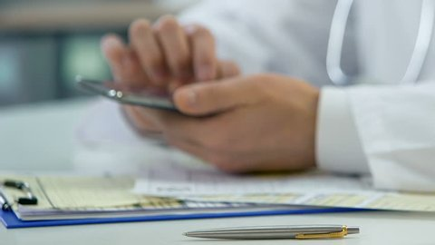 Hands of professional doctor scrolling on smartphone, consulting patient online