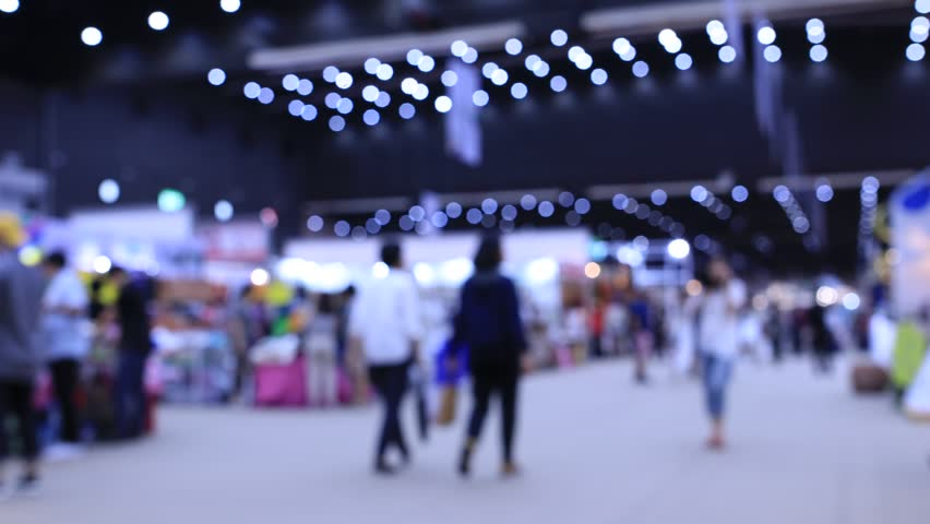 The International export import trade fair hall with many creative customers, business buyers, modern visitors, press and exhibitor stands from around the world, Blurred Background Time lapse motion