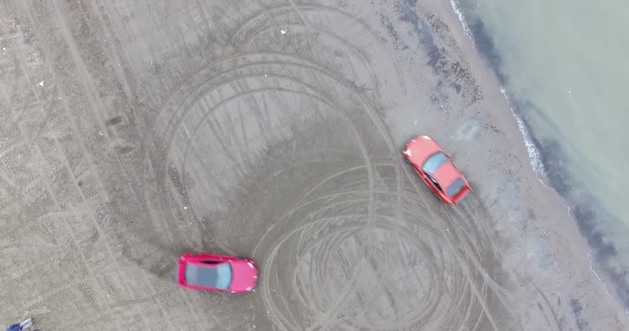 Aerial bird eye view shot of two red super sport cars drifting around at beach Two red super sport cars drifting on sand seaside beach sea water waves action no color correction ,raw footage