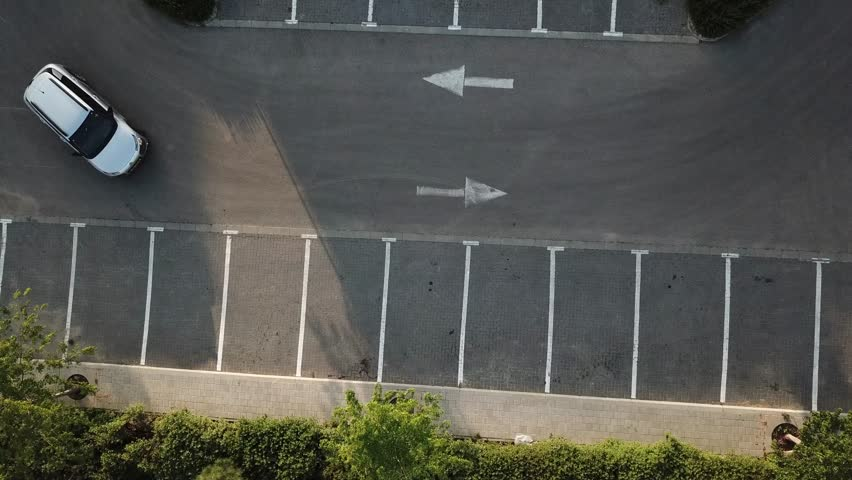 Aerial View of a man walking out of a car after reverse parking it | Shutterstock HD Video #1010118350
