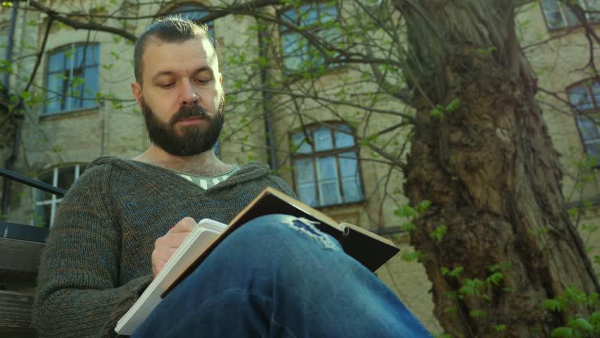 The student sits in a park next to a tree on a sunny morning, reads a book and writes in a notebook | Shutterstock HD Video #1010127170