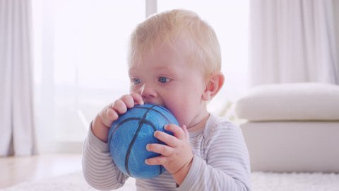White toddler boy holding and chewing ball, close up