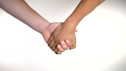 4K inter-racial couple man and woman white and black holding hands against white background, lovers embrace.