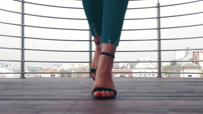 Women's legs in fashionable shoes go to the balcony | Shutterstock HD Video #1010148350