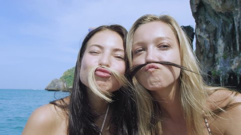 Best friends hang out on long tail boat at Phi Phi Islands, best friends portrait of them using their hair a moustache. Slow motion.